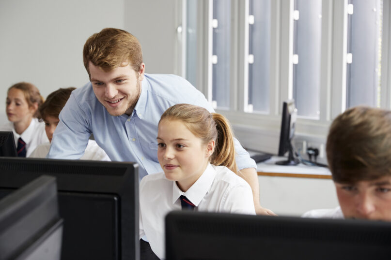 Teenage Students Wearing Uniform Studying In IT Class